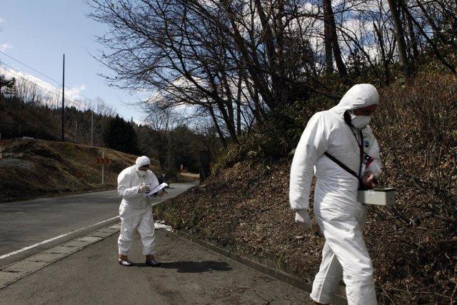 Dos operarios supervisan la zona tras el tsunami de Fukushima